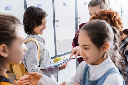 Photo for Schoolboy holding apple and notebook near friend pointing with finger in school hall - Royalty Free Image