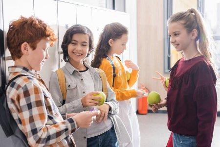 Photo pour Des écoliers joyeux avec des pommes qui parlent près des casiers pendant le freinage à l'école - image libre de droit