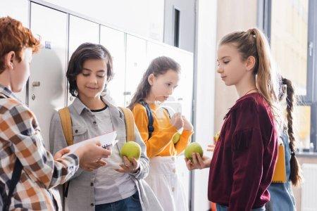 Photo pour Écolier avec pomme fraîche debout près des amis avec ordinateur portable et sacs à dos dans le hall de l'école - image libre de droit