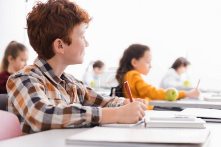 Schoolboy writing on notebook near laptop on blurred foreground in classroom