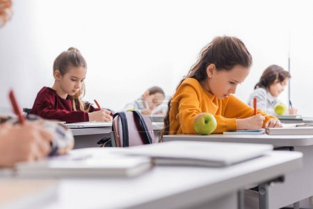 Photo for Schoolgirl writing near apple and book on desk in classroom - Royalty Free Image