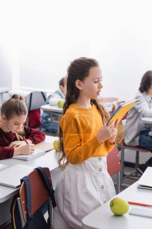 Photo pour Lecture écolière à partir d'un ordinateur portable près d'appareils, de pommes et de camarades de classe sur fond flou en classe - image libre de droit