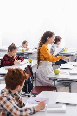 Photo pour Écolière souriante avec cahier pointant avec la main des amis proches écrivant sur des cahiers en classe - image libre de droit