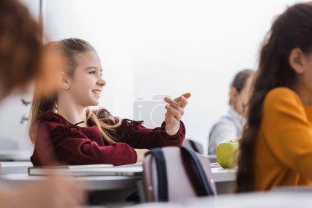 Alumno positivo sentado cerca de manzana, libro y portátil en primer plano borroso en el aula