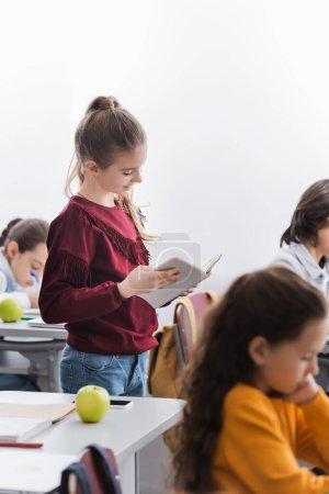 Cheerful schoolgirl reading book near classmates in classroom