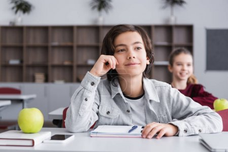 Smiling pupil looking away near devices, apple and notebook on desk