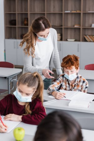 teacher in medical mask pointing with finger near schoolkid writing in notebook during lesson