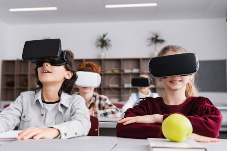 schoolchildren in vr headsets during lesson in classroom, blurred background