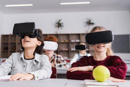 Foto de Escolares con auriculares vr durante la lección en el aula, fondo borroso - Imagen libre de derechos