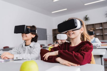Photo for Happy schoolchildren gaming in vr headsets during lesson, blurred background - Royalty Free Image