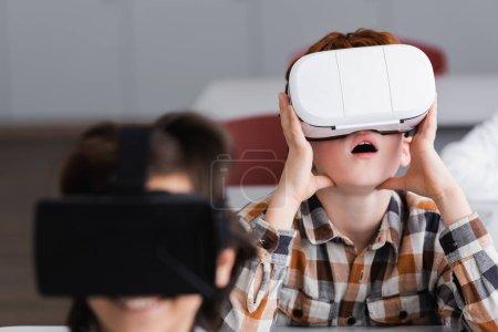 Photo pour Garçon surpris en utilisant vr casque près de camarade de classe sur le premier plan flou - image libre de droit