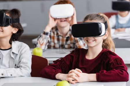 cheerful schoolkids gaming in vr headsets in classroom, blurred background