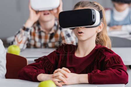 Photo for Amazed schoolgirl gaming in vr headset near classmates on blurred background - Royalty Free Image