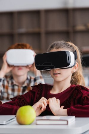 schoolgirl in vr headset near apple, book, and boy on blurred background