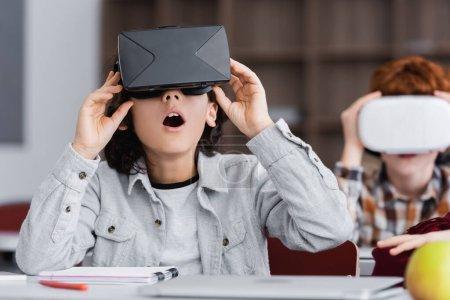 Photo pour Choqué écolier toucher vr casque tandis que le jeu à l'école sur fond flou - image libre de droit