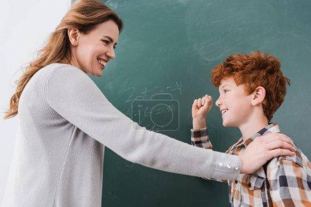 Photo pour Enseignant souriant touchant épaule de l'écolier montrant geste de victoire près de tableau noir - image libre de droit