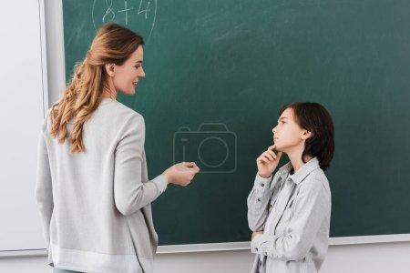 thoughtful schoolboy looking at smiling teacher near chalkboard