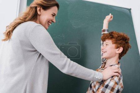 Photo pour Excité écolier montrant gagner geste près de tableau noir et professeur heureux - image libre de droit