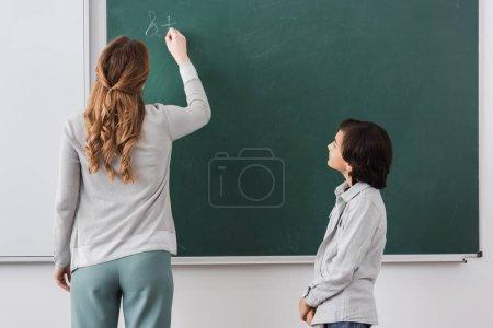Photo pour Vue arrière de l'enseignant écrivant sur le tableau près de l'écolier - image libre de droit