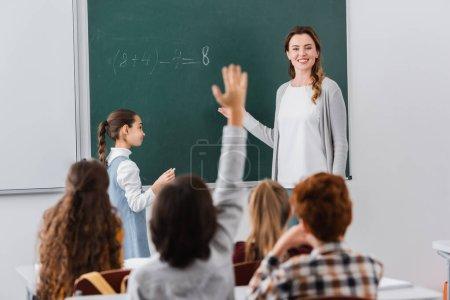Photo pour Enseignant souriant regardant écolier levant la main sur le premier plan flou - image libre de droit