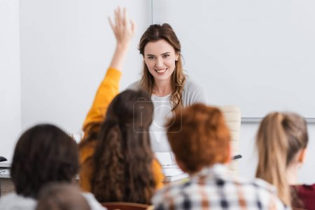 Photo for Back view of pupils near cheerful teacher in classroom, blurred foreground - Royalty Free Image