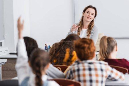 Photo pour Enseignant souriant pointant du doigt à l'écolière levant la main sur le premier plan flou - image libre de droit