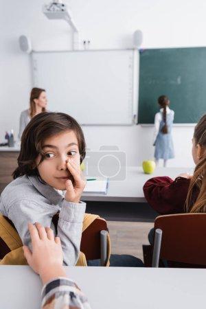 Photo pour Écolier chuchotant à camarade de classe près de fille et enseignant sur fond flou - image libre de droit