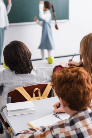back view of pupils writing during lesson in classroom, blurred background