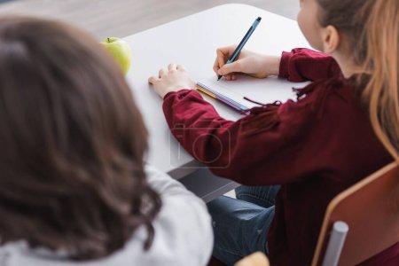 Photo pour Écolière écrit dans un cahier pendant la leçon près d'un camarade de classe au premier plan flou - image libre de droit