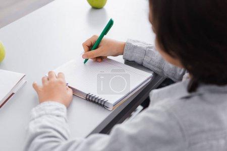 Photo pour Écriture d'écolier avec stylo dans un cahier pendant le cours à l'école, premier plan flou - image libre de droit