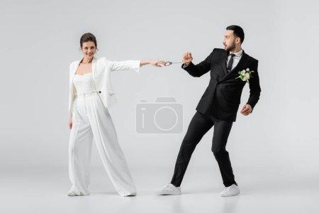 Photo pour Mariée positive tirant les menottes du marié musulman sur fond blanc - image libre de droit