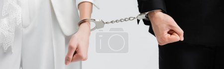Cropped view of groom and bride in handcuffs isolated on grey, banner
