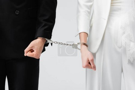 Cropped view of bride and groom in handcuffs isolated on grey