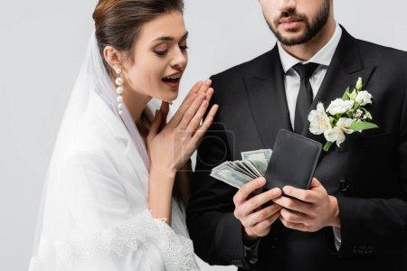 Novia emocionada mirando al novio con dólares y billetera aislada en gris