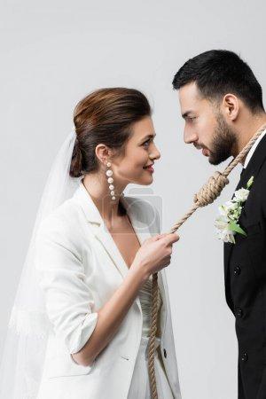 Photo pour Vue latérale de la mariée souriante tirant la corde autour du cou du marié musulman isolé sur gris - image libre de droit
