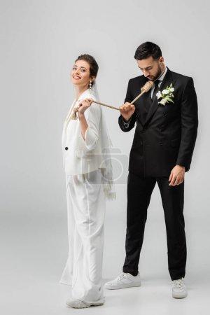 Photo pour Mariée souriante en vêtements de mariage et voile tirant nœud glissant sur le cou du marié musulman sur fond blanc - image libre de droit