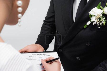Vue recadrée de la mariée signant un contrat de mariage près du marié isolé sur gris