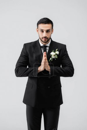 Photo pour Marié arabe avec des mains priantes regardant la caméra isolée sur gris - image libre de droit