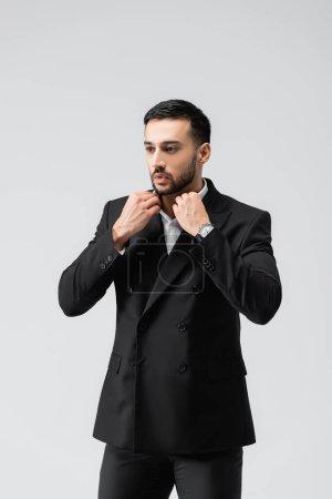 Photo pour Élégant homme musulman ajustant collier tout en regardant loin isolé sur gris - image libre de droit