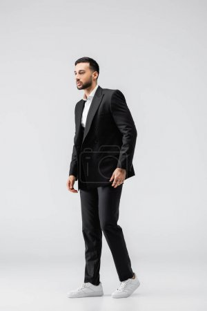 Photo for Full length view of young arabian man in black, elegant suit and sneakers looking away on grey - Royalty Free Image