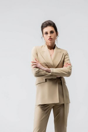 sensual woman in trendy pantsuit posing with crossed arms isolated on grey