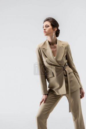 elegant woman in beige pantsuit looking away while standing isolated on grey