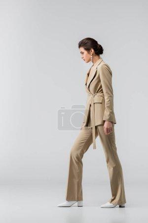 Photo pour Longueur totale de la femme en pantalon élégant debout sur le gris, vue latérale - image libre de droit