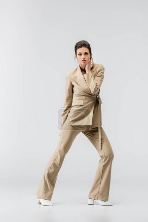 full length view of fashionable woman touching neck and looking at camera while standing on grey