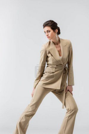 pretty woman in trendy pantsuit looking away while posing isolated on grey