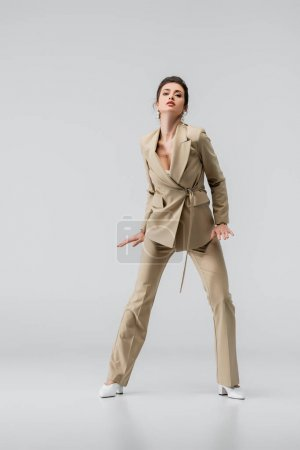 Photo for Full length view of sensual woman in beige pantsuit looking at camera on grey - Royalty Free Image