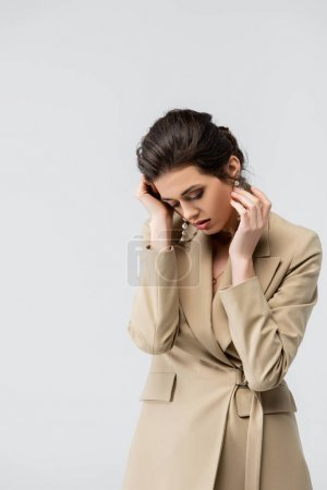 Photo for Sensual, stylish woman touching face while posing with bowed head isolated on grey - Royalty Free Image