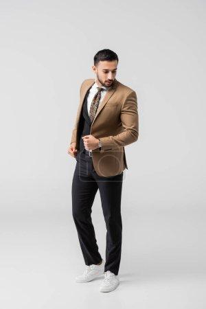 Photo pour Vue pleine longueur de brune arabian homme en costume à la mode et baskets posant sur gris - image libre de droit