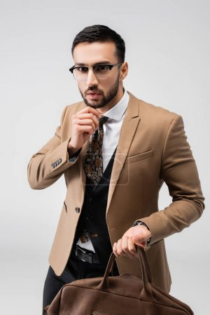 Photo for Fashionable muslim man holding leather bag while looking at camera isolated on grey - Royalty Free Image