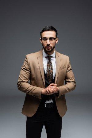 Photo pour Homme musulman en costume élégant et lunettes debout avec les mains serrées sur gris - image libre de droit
